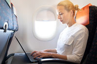 Attractive caucasian female passenger working at modern laptop computer using wireless connection on board of commercial airplane flight