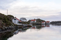 Rovaer in Haugesund, Norway - januray 11, 2018: The Rovaer archipelago in Haugesund, in the norwegian west coast. Pier and fishing boat, houses by the sea.