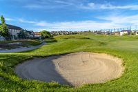 Close up of sand bunker on golf course under blue sky and clouds on a sunny day