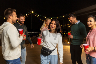 friends with drinks dancing at rooftop party