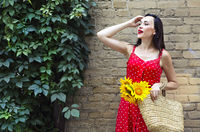 Beautiful young woman in red polka dots dress holding basket with sunflowers