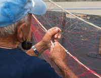 Senior fisherman repairs fishing net