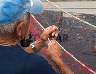 Senior fisherman repairs fishing net