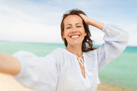 happy smiling woman taking selfie on summer beach