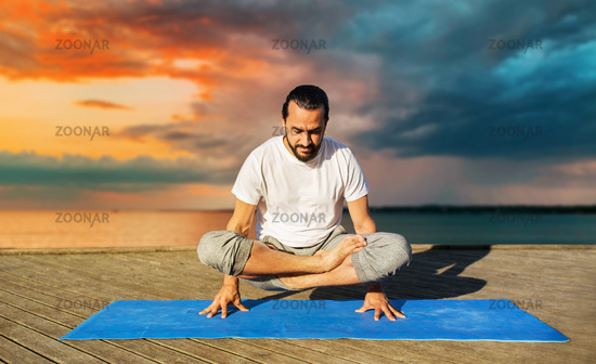 man making yoga in scale pose outdoors