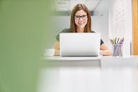 Junge Business Frau als Praktikantin am Computer