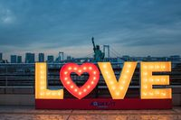 TOKYO, JAPAN - 21 FEB 2018: Love sign with lights, Japanese statue of liberty and rainbow bridge at blue hour