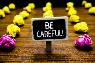 Text sign showing Be Careful. Conceptual photo making sure of avoiding potential danger mishap or harm Blackboard crumpled papers several tries mistake not satisfied wooden floor.