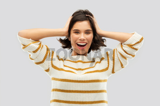 happy woman in pullover holding to her head