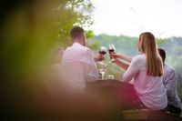 happy friends toasting red wine glass during french dinner party outdoor