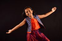 Little Girl in Indian attire with cute smile and outstretched arms posing in front of camera. Pune, Maharashtra