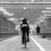 Man riding his bike in the cycling lane on Williamsburg Bridge, Brooklyn, New York City.