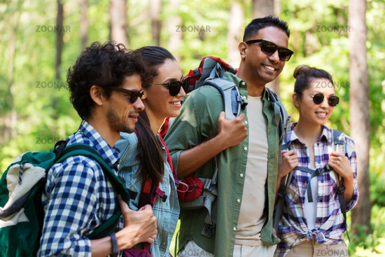 group of friends with backpacks hiking in forest