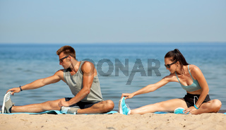 happy couple stretching legs on beach