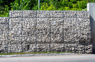 Protection fence or wall made of gabions with stones