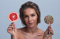 Woman with slice of grapefruit and lollipop
