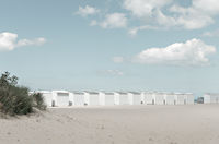 A row of white beach cabins on a summer day.
