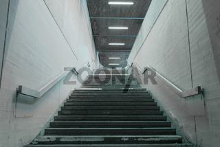 Staircase with concrete walls and metal railings