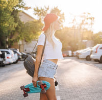 Young girl with a skateboard on a car park.