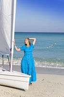 Cuba. Beautiful woman on the blue sea near the boat with a sail