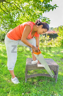 Colombian woman sawing wood outdoors with handsaw