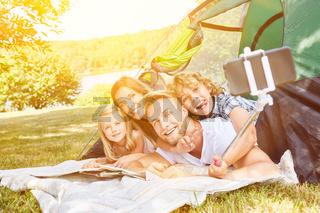 Familie macht Selfie mit Selfie Stick beim Camping