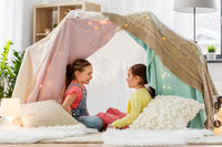 happy girls lying in kids tent and talking at home