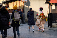 KYOTO, JAPAN - 08 FEB 2018: Beautiful young japanese Maiko with white makeup and traditional kimono walking the streets of Kyoto from behind