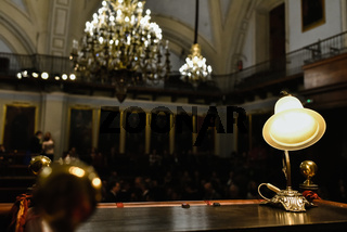 Valencia, Spain - December 8, 2018: Old lamp illuminating a wooden desk in the hemicycle of a local parliament.