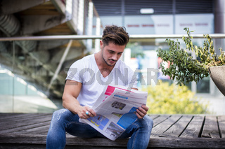 Handsome man reading newspaper outdoor in city