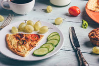 Slice of frittata with cup of coffee, grapes and muffins.