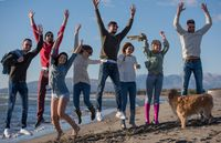 young friends jumping together at autumn beach