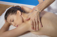 attractive spanish brunette girl getting a naked back massage by a massage professional