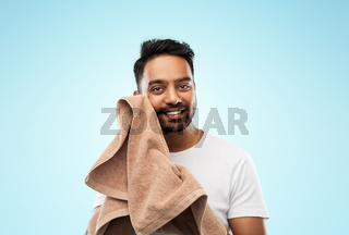 smiling indian man with towel over blue background