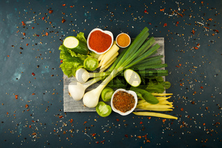 VEGETABLES ON WOODEN BOARD ON A STONE BACKGROUND. YOUNG HERBS ONIONS GARLIC GREEN BEANS YELLOW CORN ZUCCHINI BRIGHT SPICES LIE ON A DARK WOODEN BOARD ON A TEXTURED BACKGROUND.