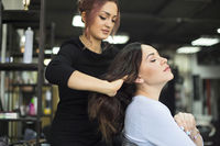 Female hairdresser setting up client's hair in beauty salon