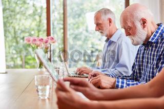 Gruppe Senioren mit Laptop im Computerkurs