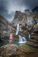 Traveller stands in awe, moody skies, limestone cliffs, waterfalls and blue waterholes