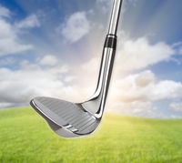 Chrome Golf Club Wedge Iron Against Grass and Blue Sky Background