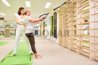 Fitnesstrainer gibt Hilfestellung beim Schlingentraining
