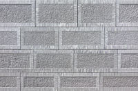 Detail of a wall of gray square sandstone with pattern