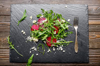 Beetroot arugula and feta cheese salad and fork on slate stone plate closeup flat lay view