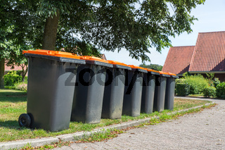 Row of gray waste containers along the street