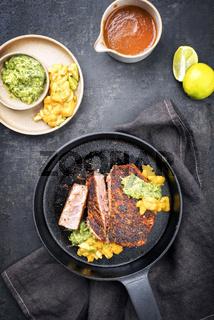Traditional exotically blackened Cajun style tuna fish fillet with mango avocado salad