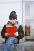 7 year old boy reading on tablet pc computer outdoors in winter