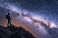 Space with Milky Way and silhouette of a woman with backpack