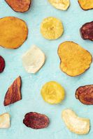 Dried fruit and vegetable chips, shot from above. Healthy vegan snack, an organic food flat lay pattern on a blue background