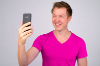 Happy young handsome man smiling while taking selfie