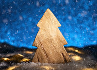 Wooden Christmas tree in front of a blue background