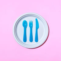 Served place with eating plastic utensil on a pastel pink background.